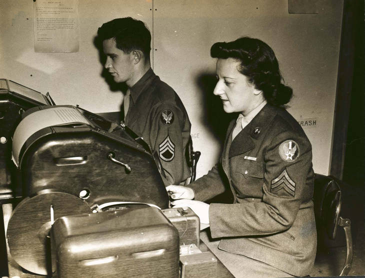 Sergeant Blanche Rubenstein and Staff Sergeant John J. Barrett handle incoming and outgoing messages at the Base Signal Center at Bradley Field.